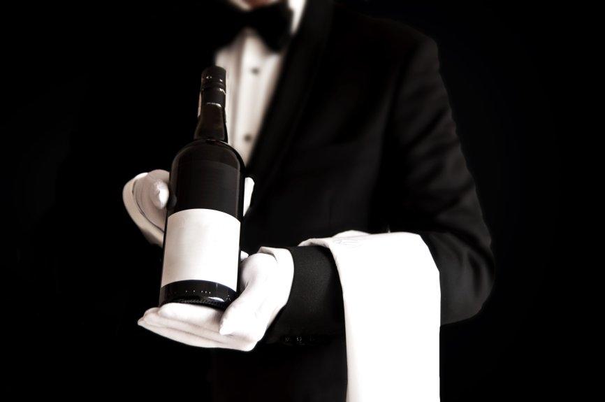 Waiter in tuxedo holding a bottle of red wine