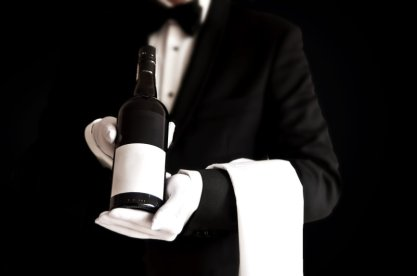 Waiter in tuxedo holding a bottle of red wine